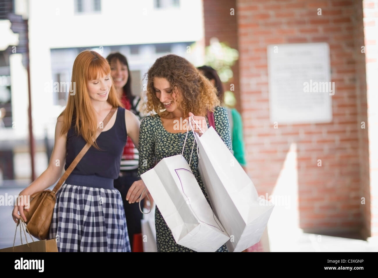 Girlfriends on shopping tour looking in bags - Stock Image