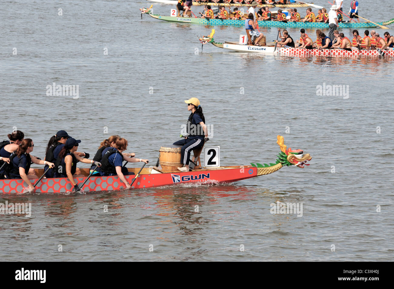 Dragon boaters rowing with drummer - Stock Image