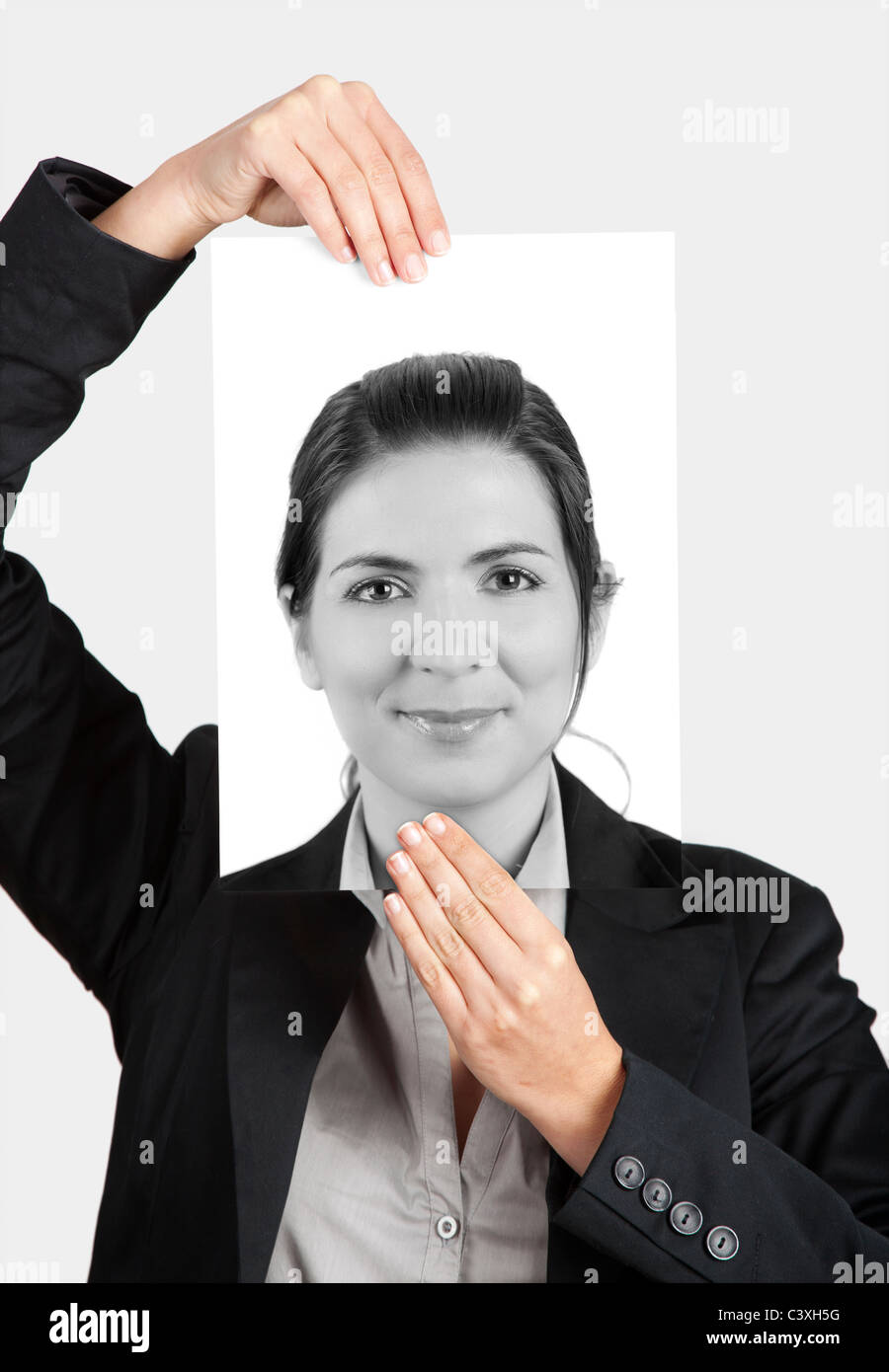 Woman holding a self portrait in front of her face - Stock Image