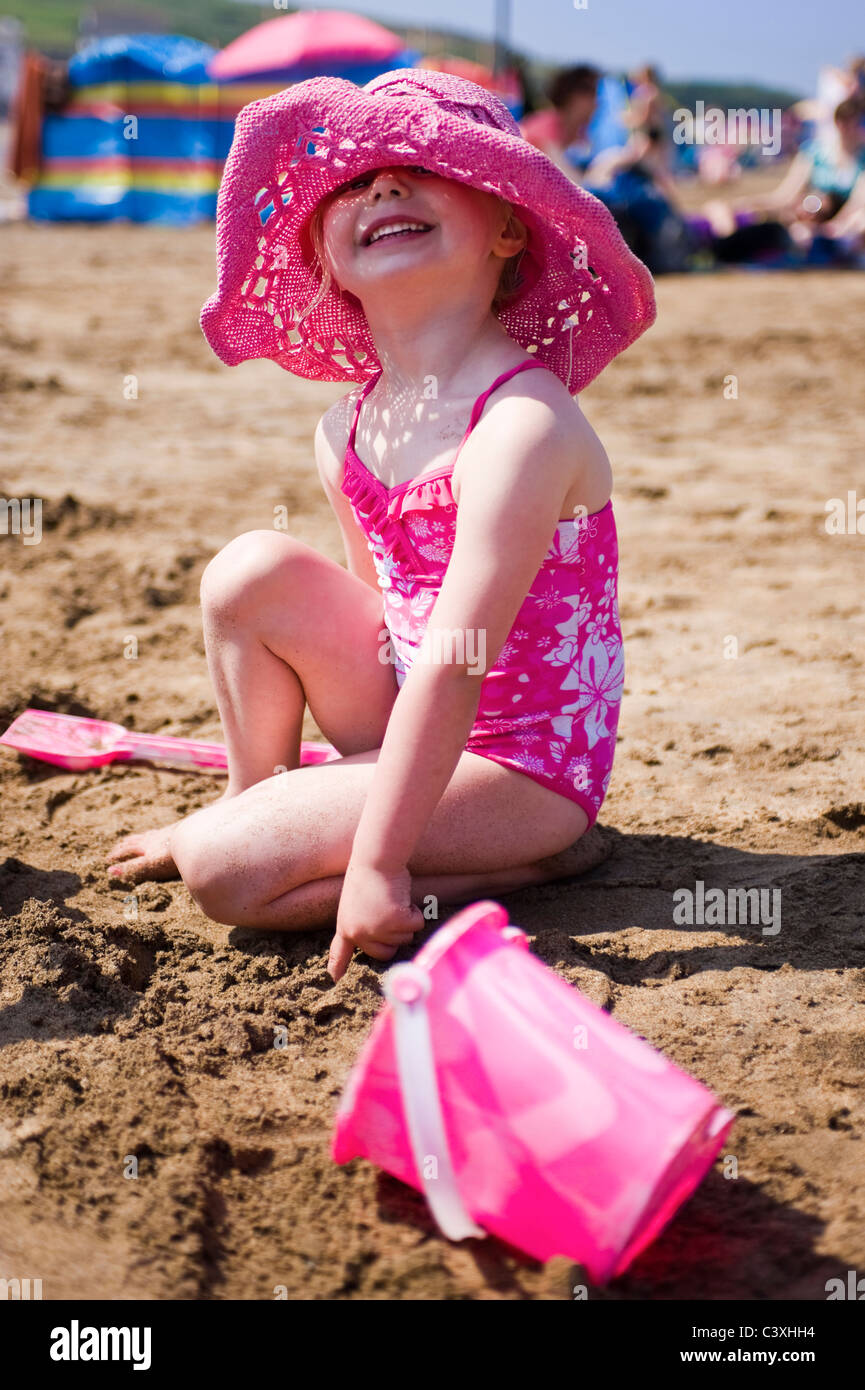 Vertical portrait of a little girl building sandcastles on the beach on a sunny day. - Stock Image