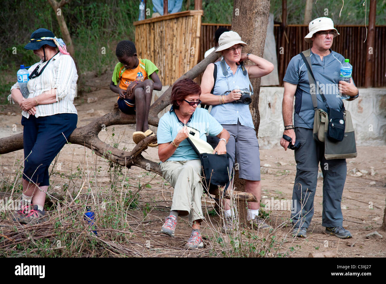 Group of tourists with camera at bull jumping ceremony, Turmi, Ethiopia, Africa - Stock Image