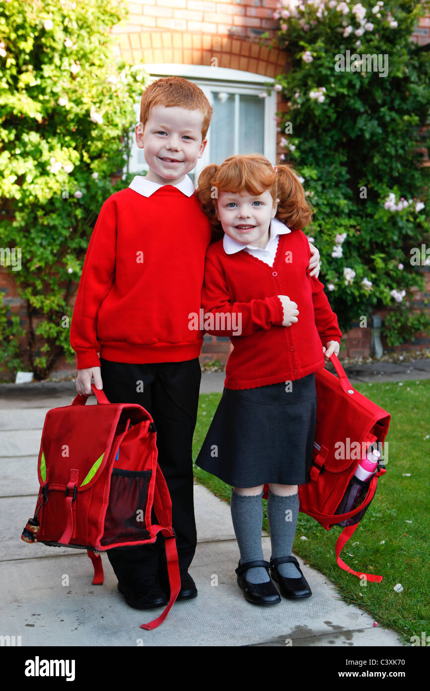 A 4 year old girl with ginger hair on her first day of school, with 6 year old brother. Both in school uniforms. - Stock Image