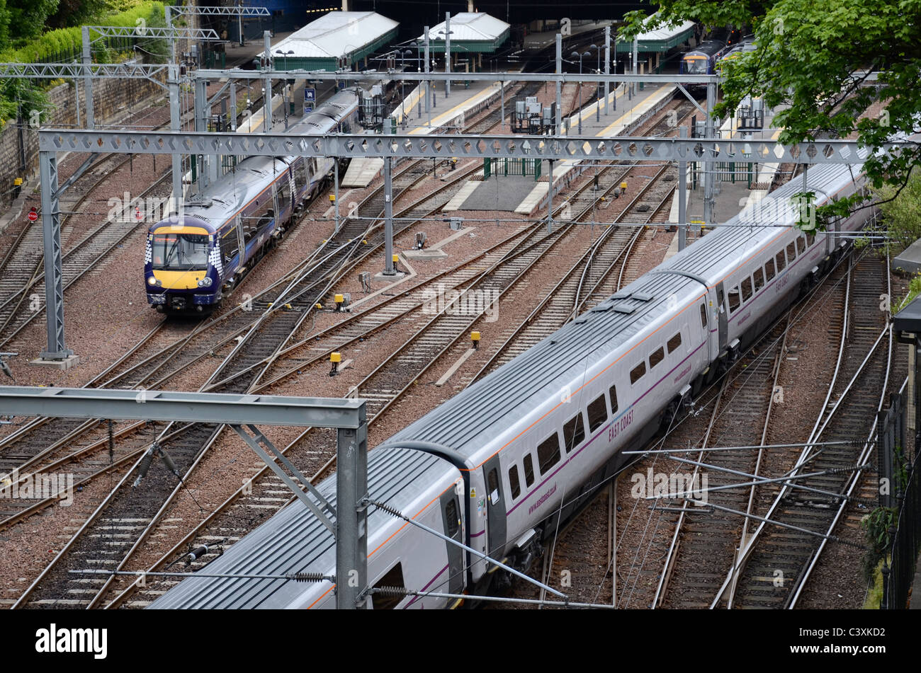 An East Coast train arrives at Edinburgh Waverley as a Scotrail train departs. - Stock Image