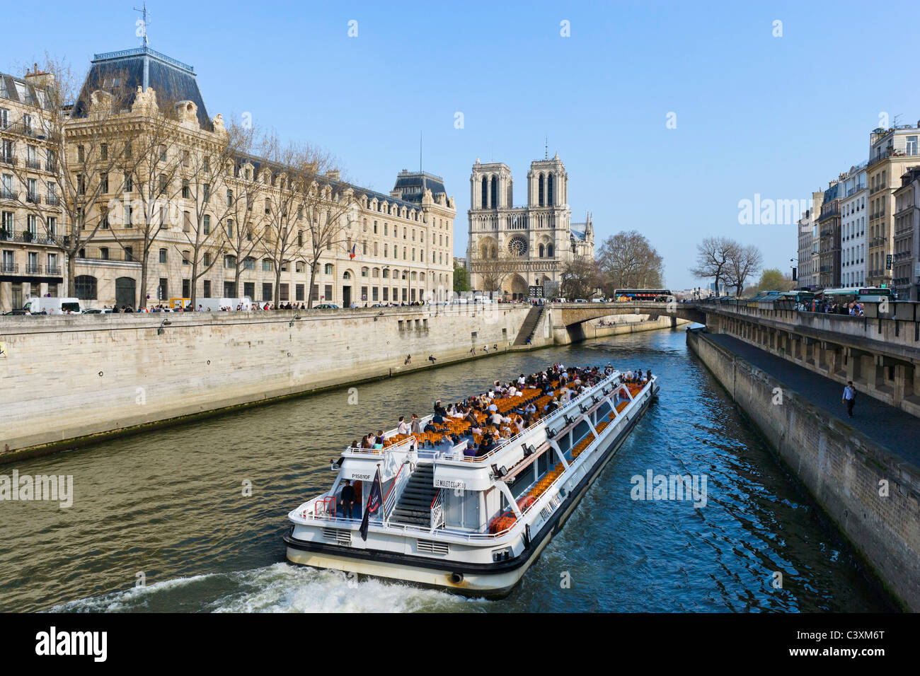 Cruise boat on the River Seine from the Pont St Michel with the Cathedral of Notre Dame behind, Paris, France - Stock Image