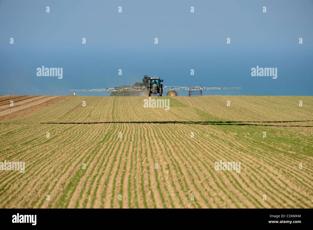 Tractor sprays a field, Manneville-ès-Plains, Normandy, Seine-Maritime, France - Stock Image