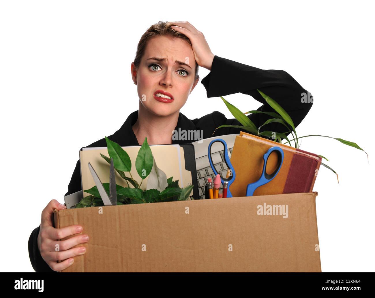 Upset businesswoman carrying office belongings after loosing job - Stock Image