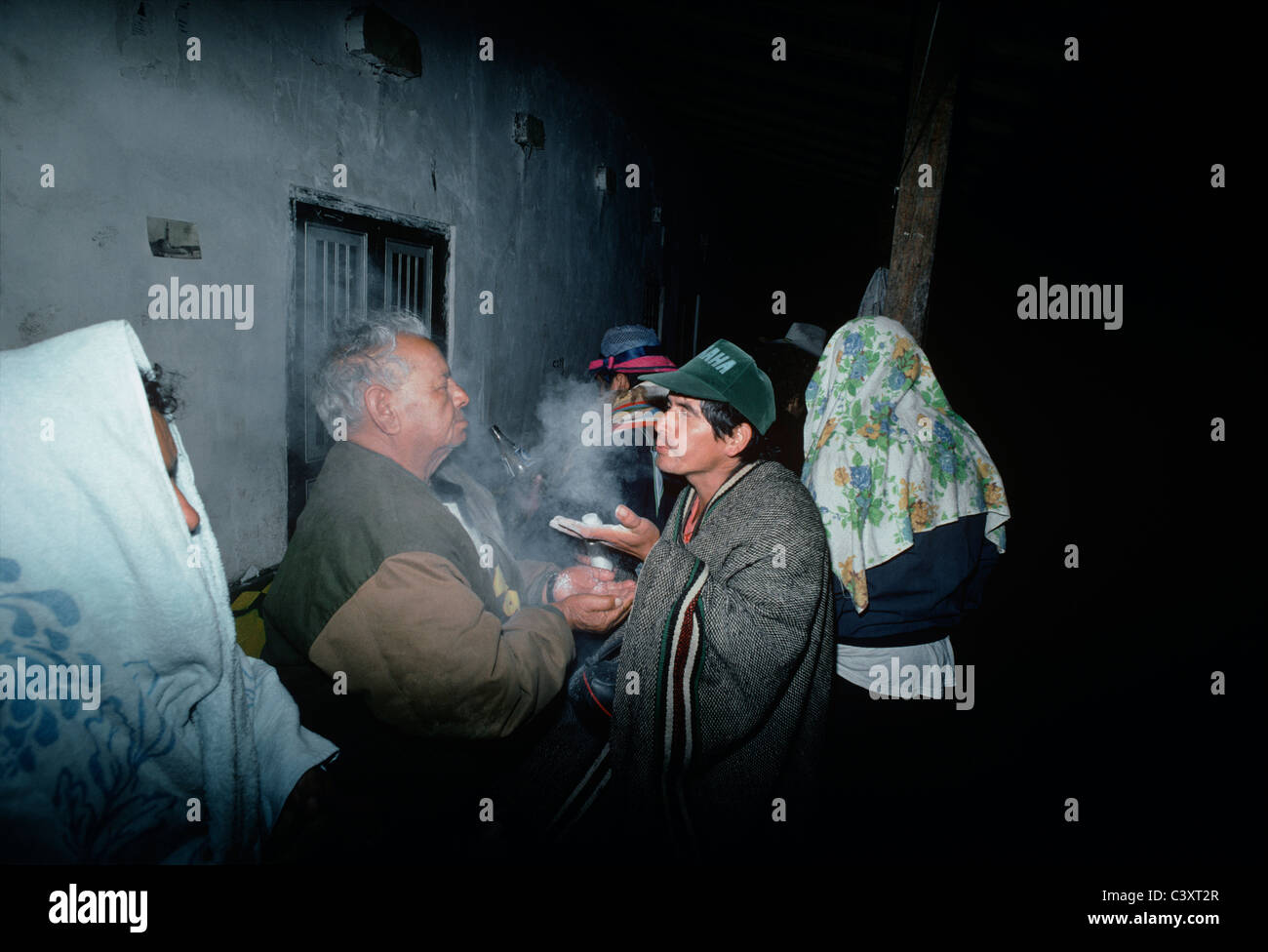 Peruvian folk healer (curandero) blowing a mystical white powder into the face of a man wishing for spiritual cleansing. - Stock Image