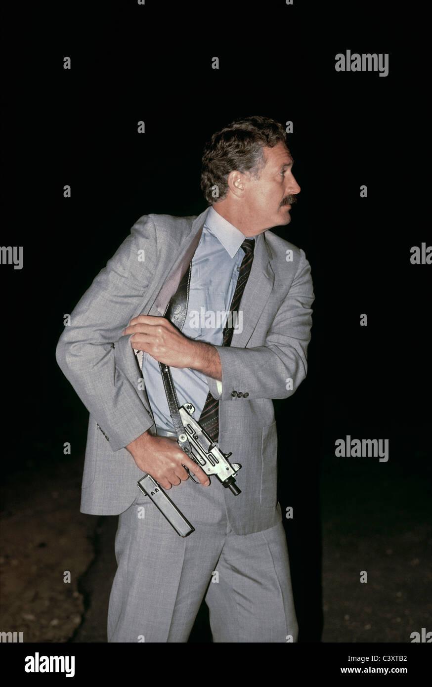 Israeli Secret Service agent draws an uzi pistol from his shoulder holster. IsraelStock Photo