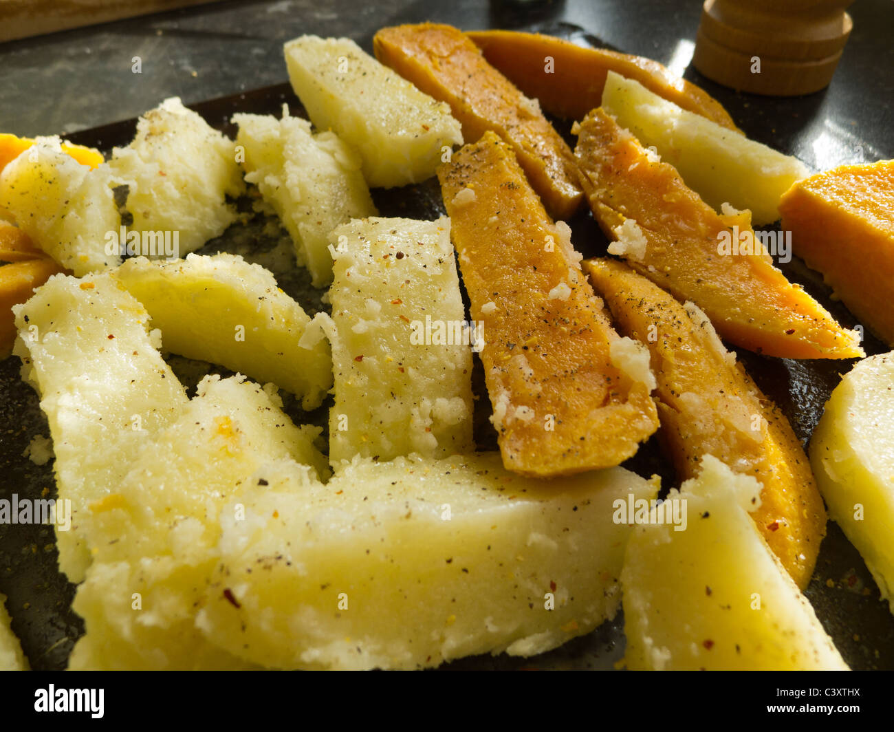 Home-made chips on baking sheet ready for cooking - Stock Image