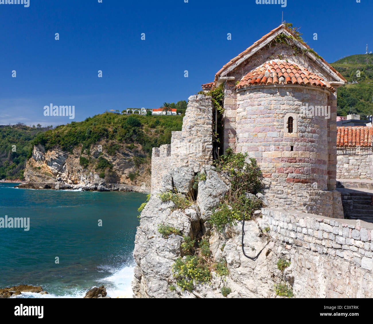 historic watch tower built of rough stone on a old city wall overlooking the sea in Montenegro - Stock Image