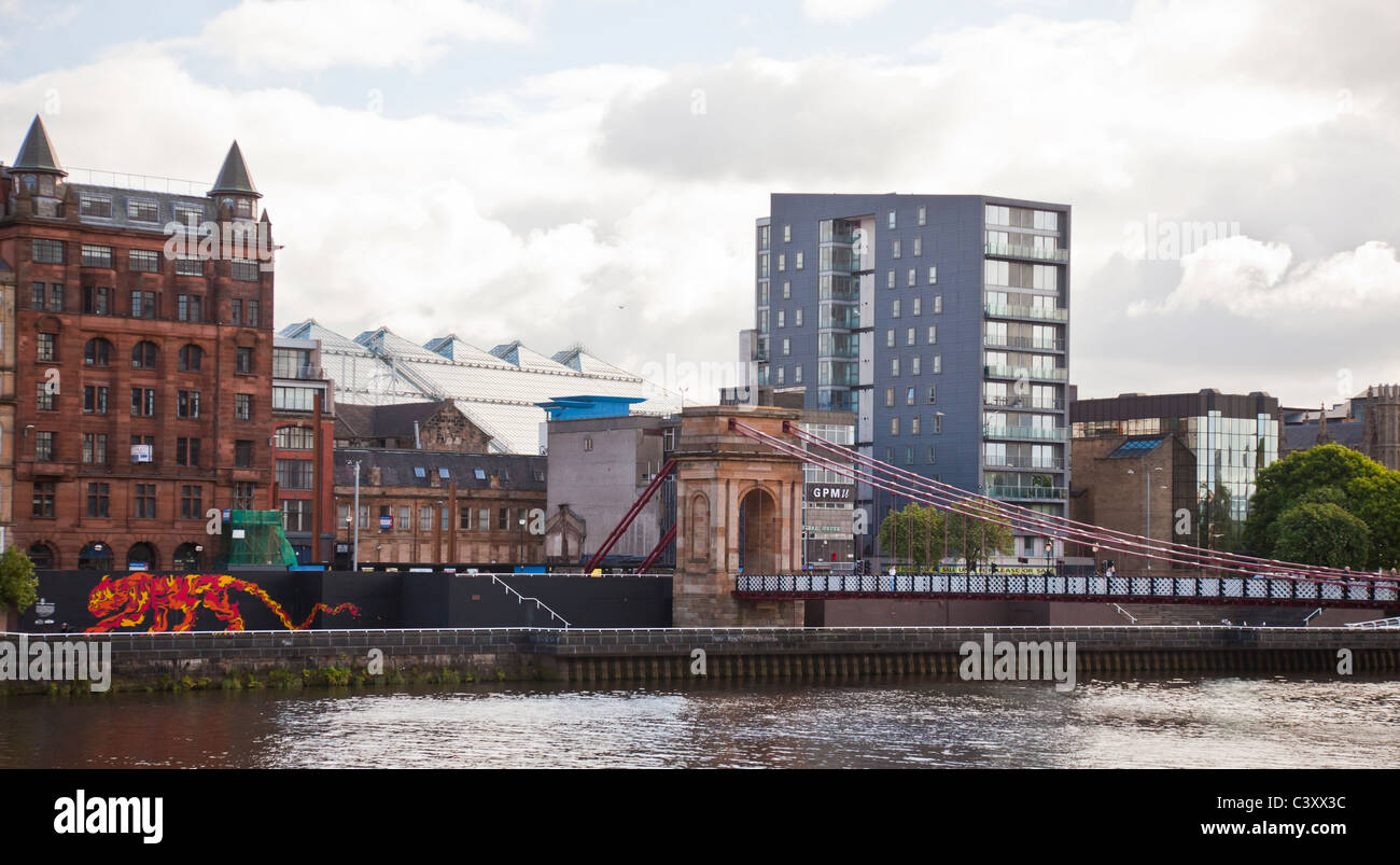 St Andrews Suspension Bridge over the River Clyde in Central Glasgow with the Tiger Beer mural by John McFaul of - Stock Image