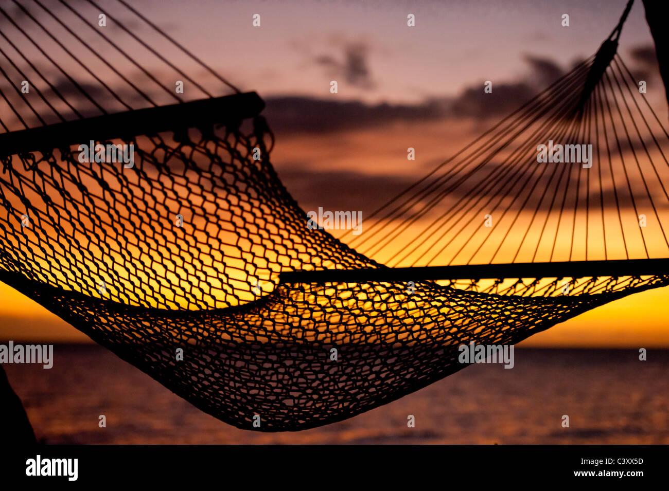 silhouette of hammock on beach overlooking ocean at sunset - Stock Image