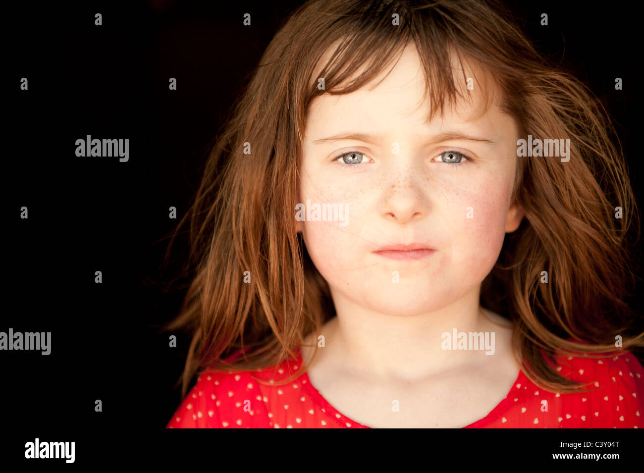 little girl looking at camera with serious facial expression - Stock Image