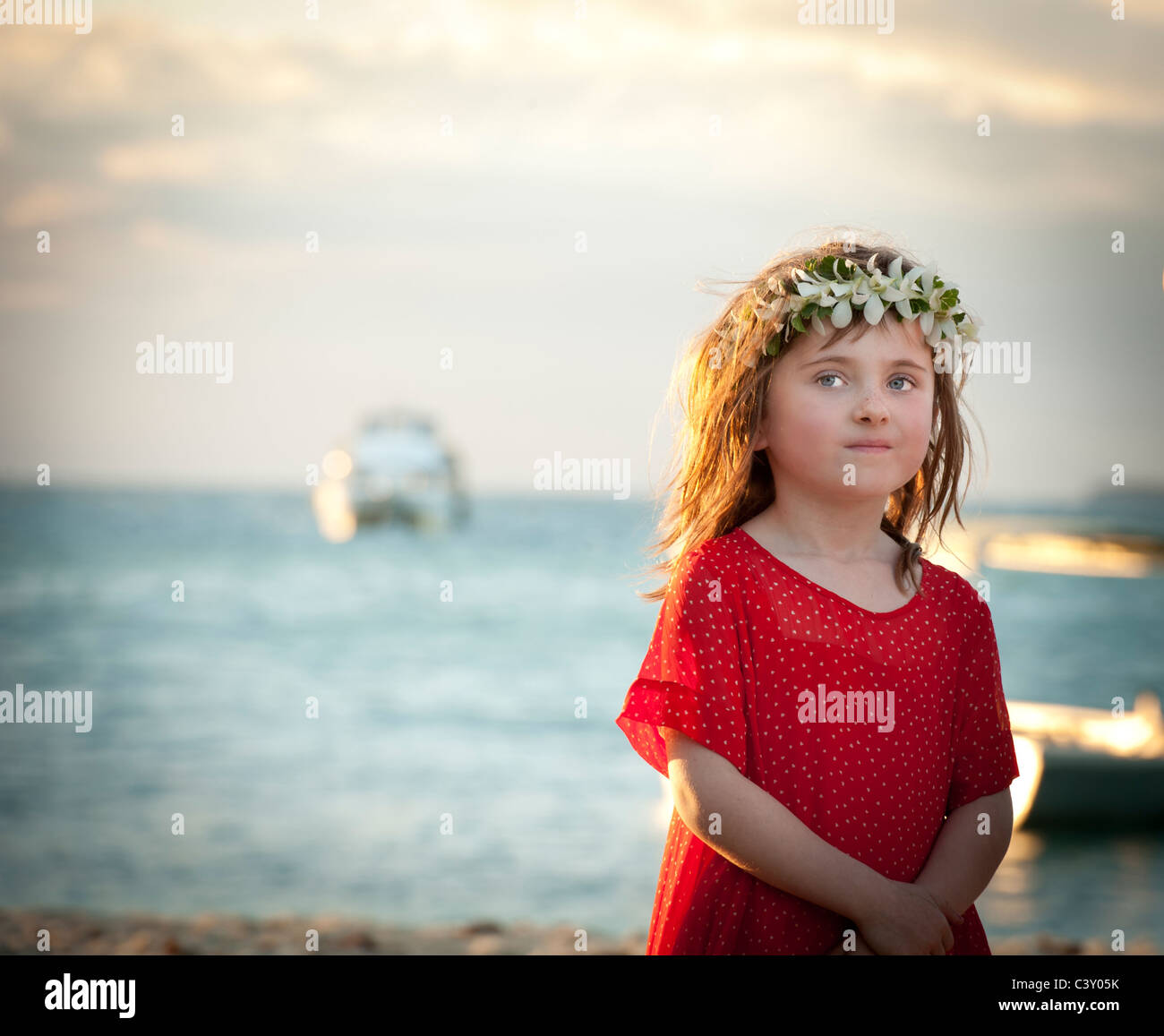 little girl with flowers in her hair and red dress innocently looking off into distance - Stock Image
