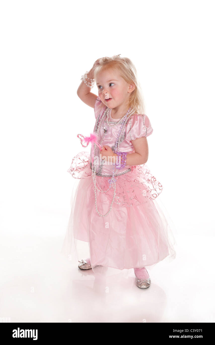 pretty cute little girl dressed in pink princess dress having fun and funny face against white background Stock Photo