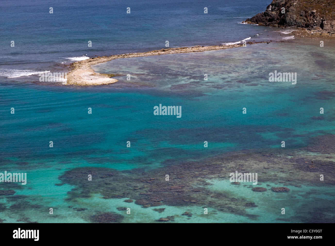 Coral reefs below clear turquoise water and sandbar protruding from rocky shore in Caribbean - Stock Image