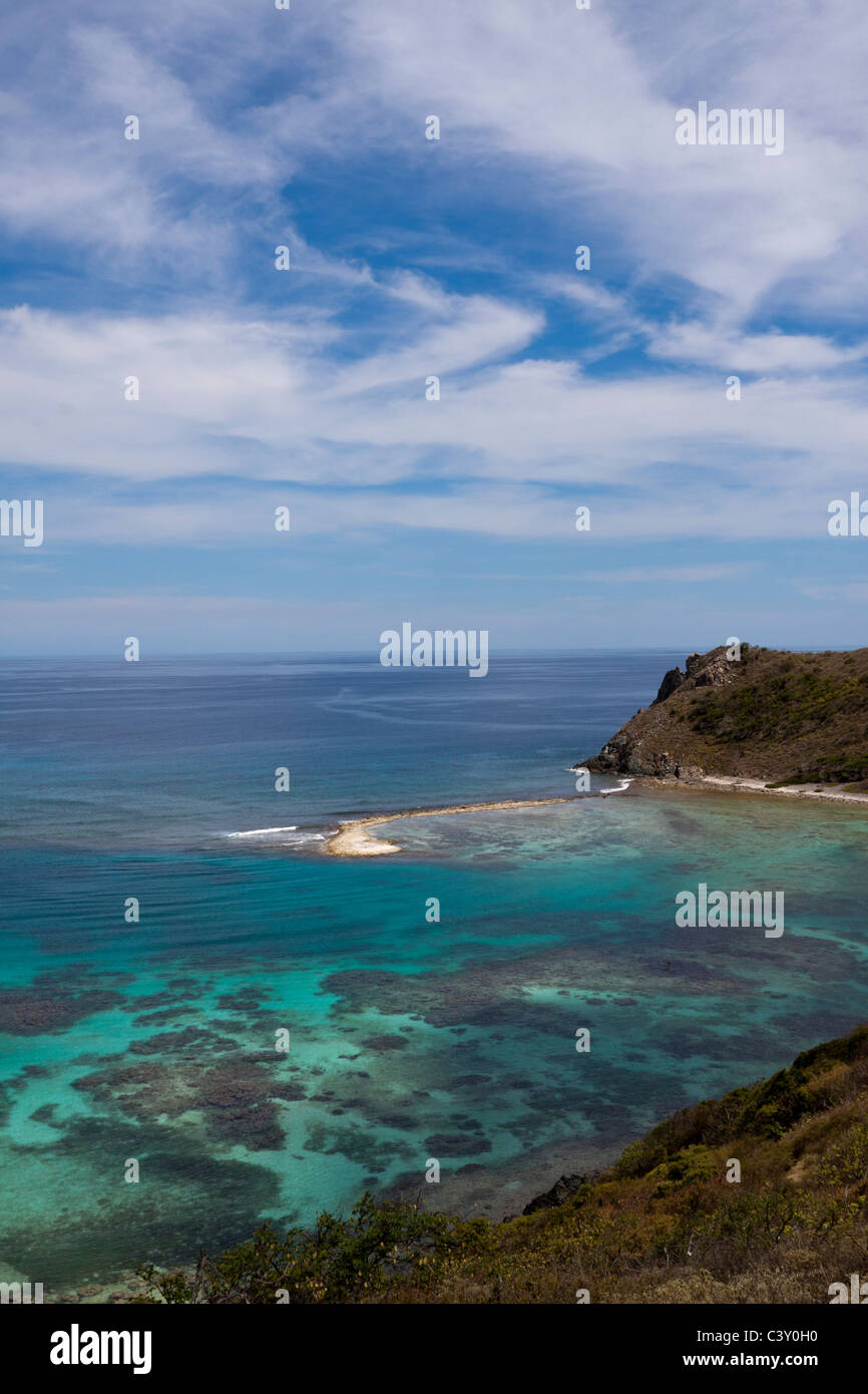 Swirling clouds matching pattern of sandbar and coral reefs below turquoise water along rocky shore in British Virgin - Stock Image