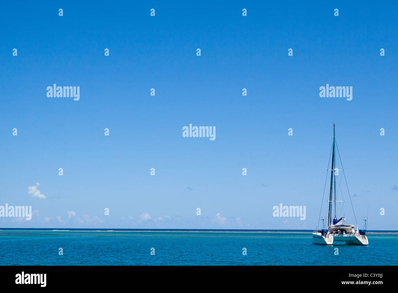 Sparse image of catamaran sailboat moored in turquoise water and blue sky in Caribbean Sea - Stock Image