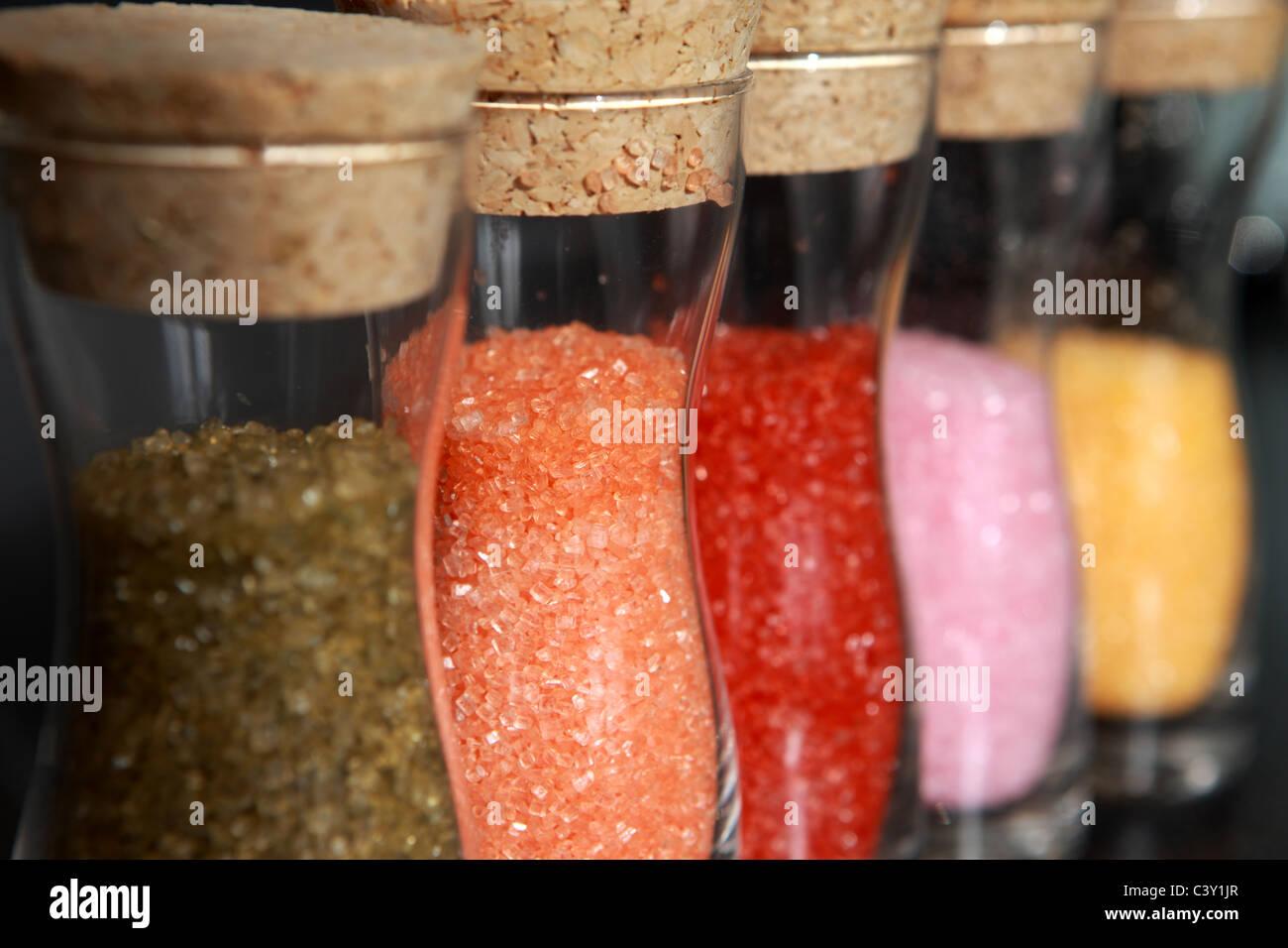 Coloured sugar in glass jars - Stock Image