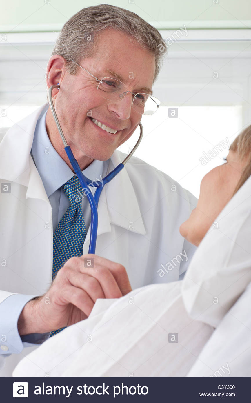 Doctor listening to patient's heartbeat in hospital room - Stock Image