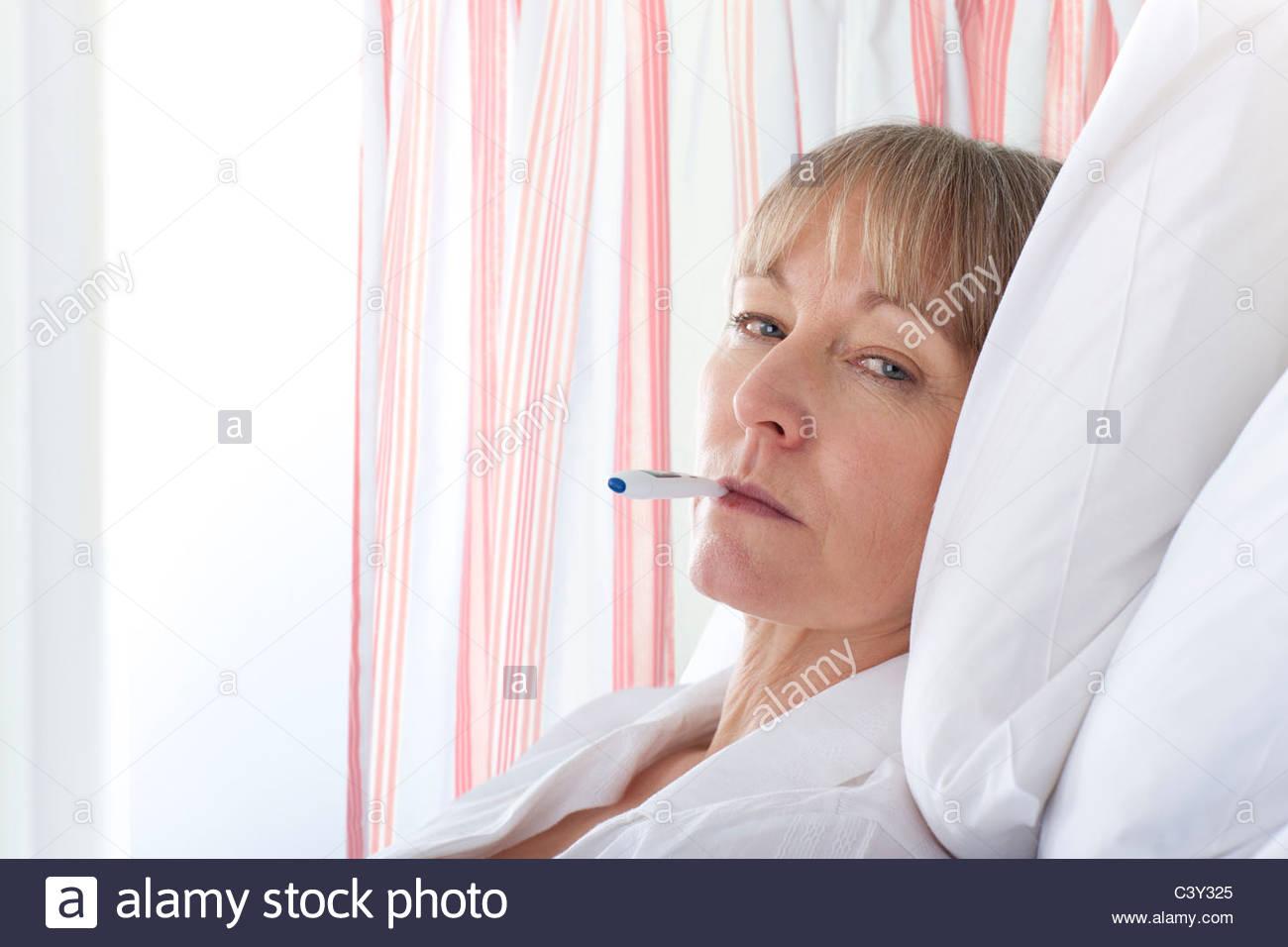 Patient having temperature taken in hospital room - Stock Image