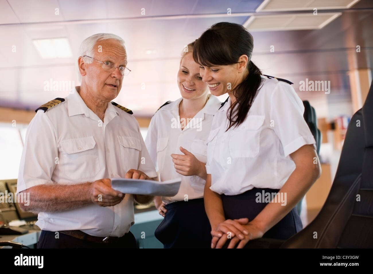 Captain giving advices to his assistants - Stock Image