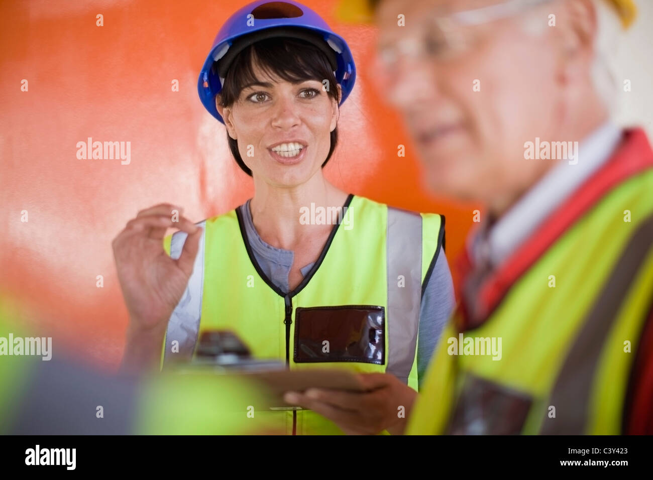 Female architect talking to builders - Stock Image