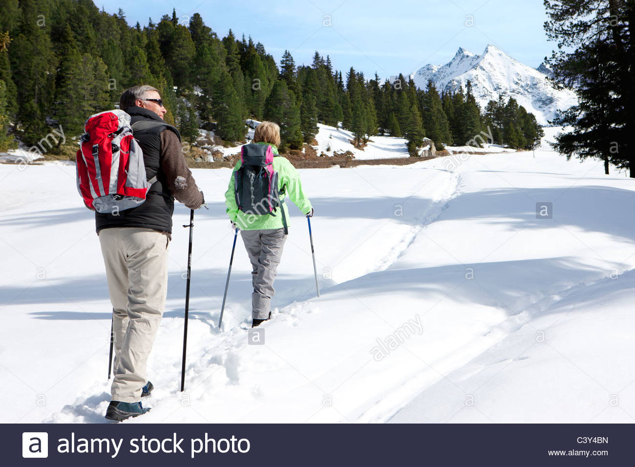 Couple hiking on trail in snow covered wilderness - Stock Image