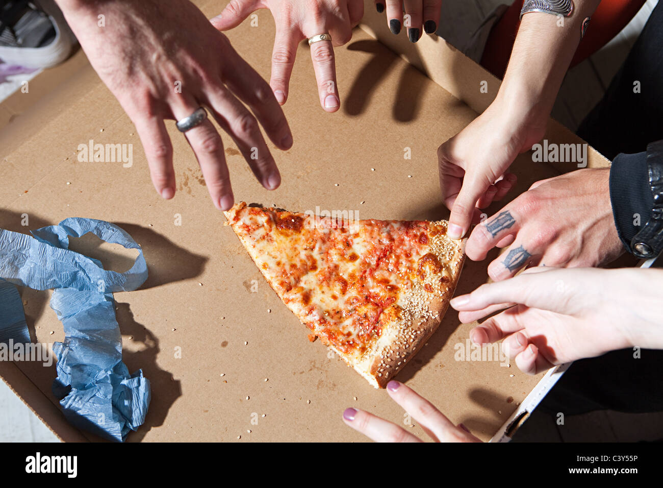 People taking slice of pizza at party - Stock Image