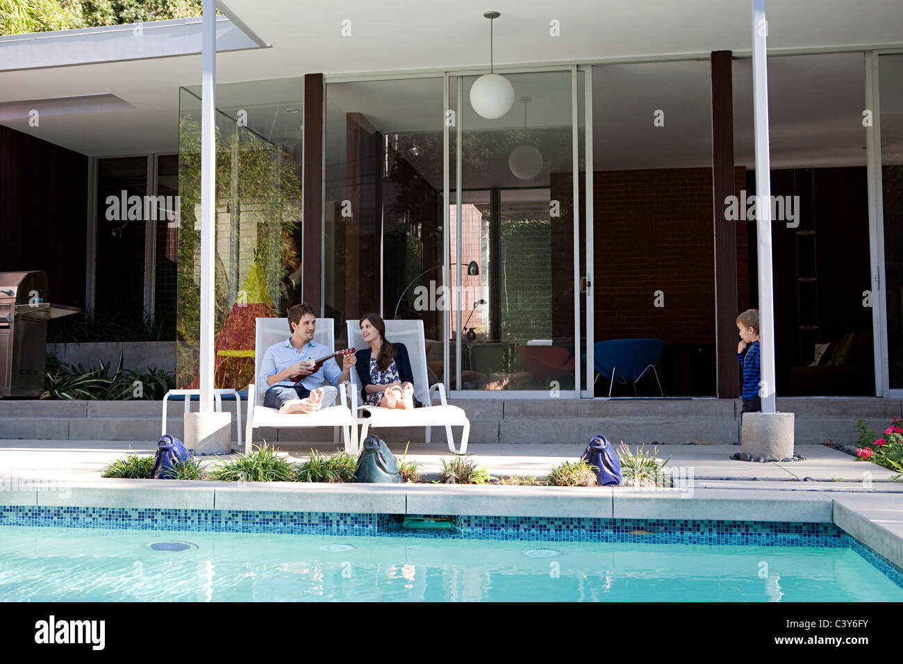 Parents with son at poolside - Stock Image