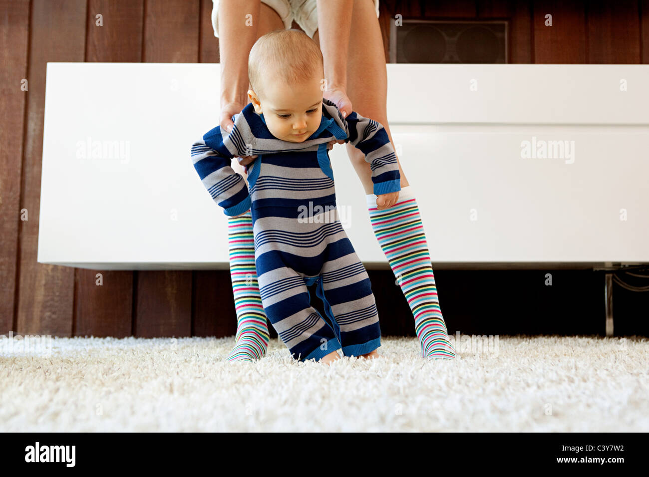 Mother helping baby son take first steps - Stock Image