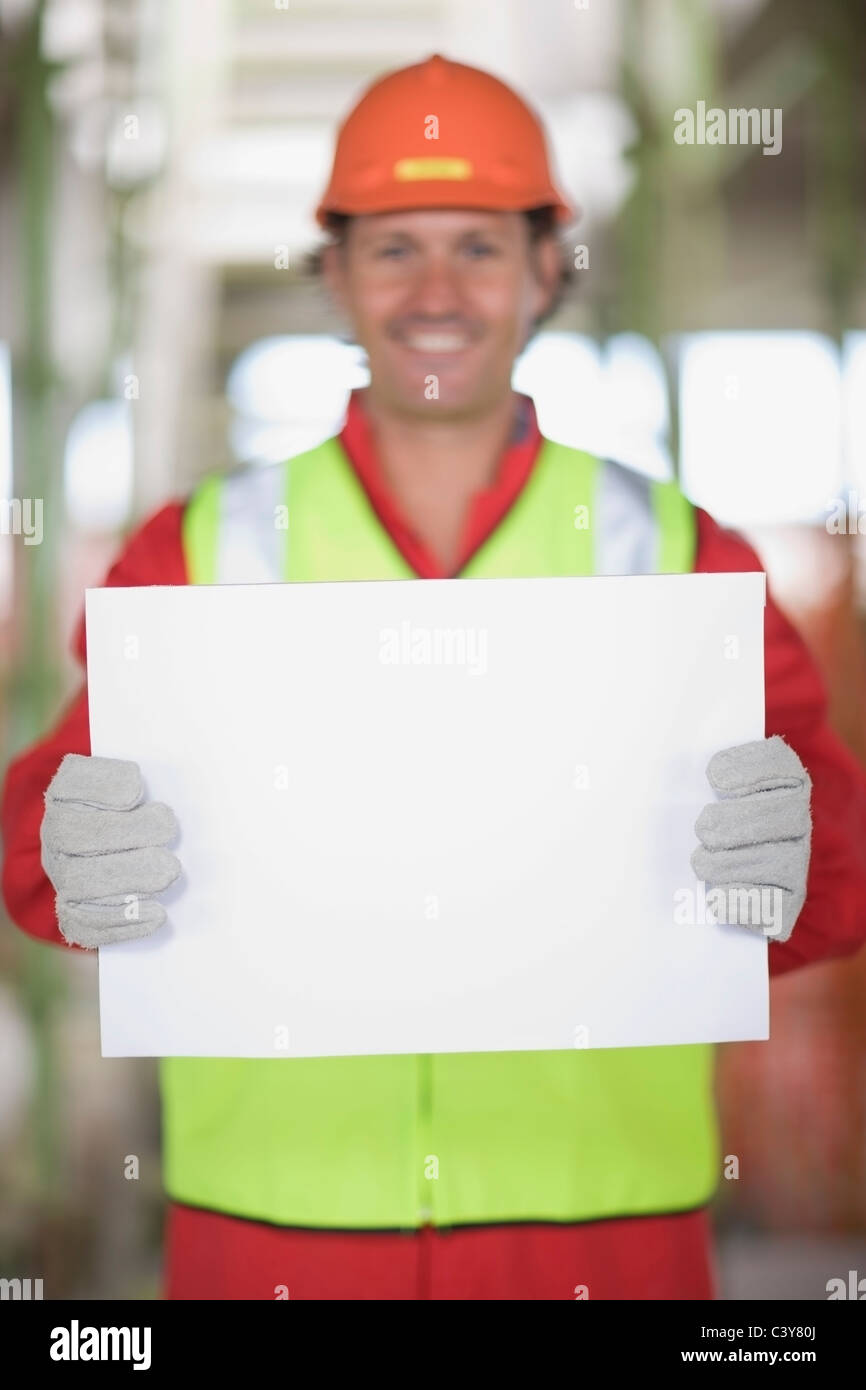 Worker holding an empty sheet of paper - Stock Image