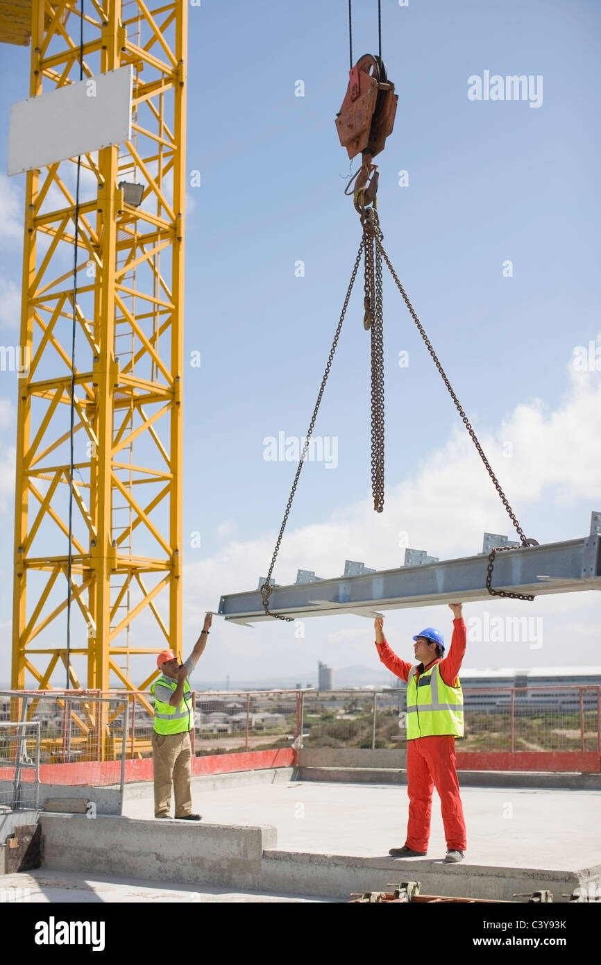 Crane and workers on construction site - Stock Image