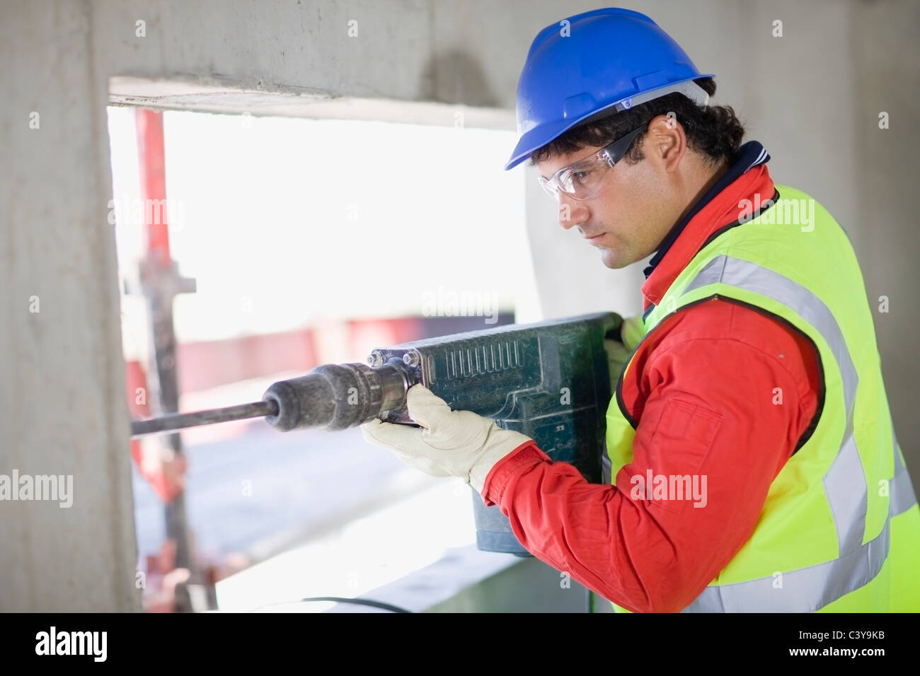 Building worker handling a power drill - Stock Image