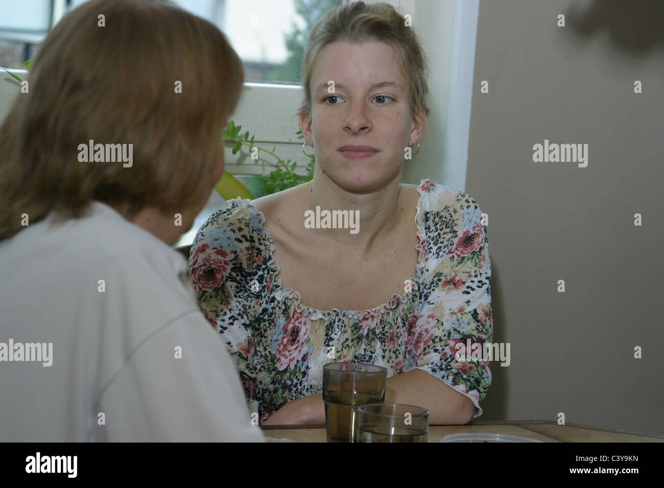 2 People talking one worried and sit at table - Stock Image