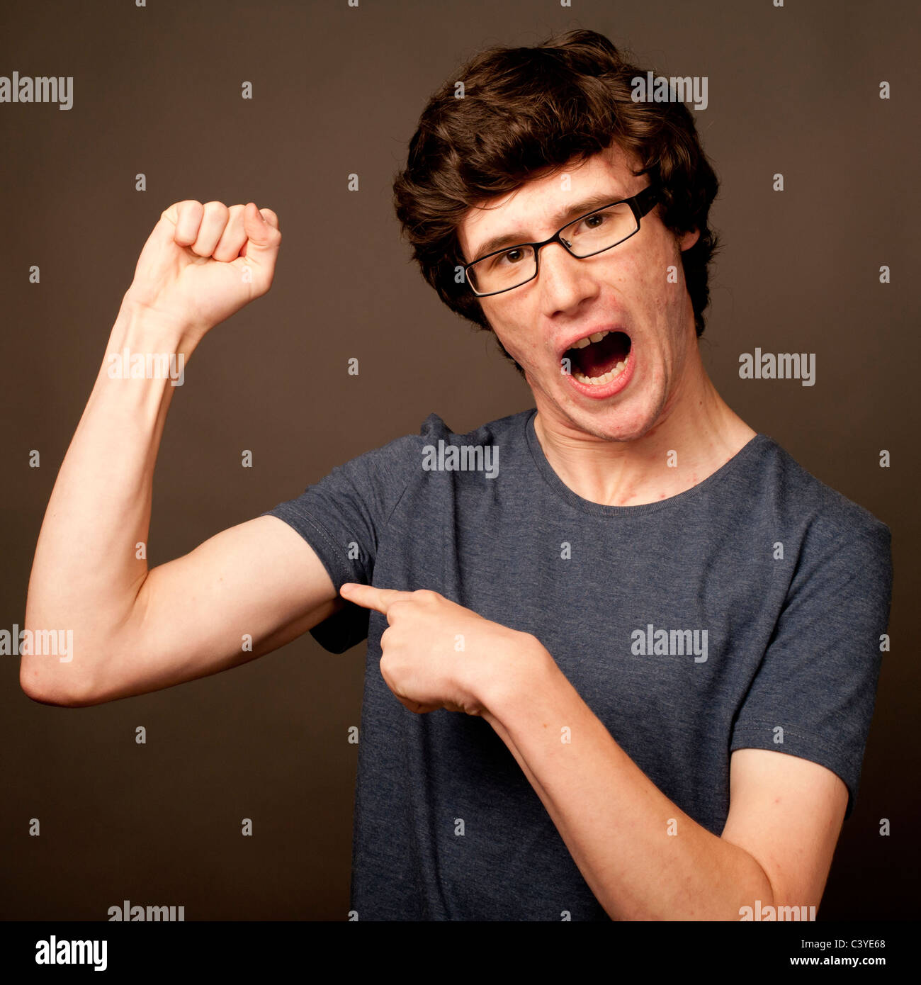a weak feeble geek nerd young man with thin arms wearing glasses flexing his muscles - Stock Image