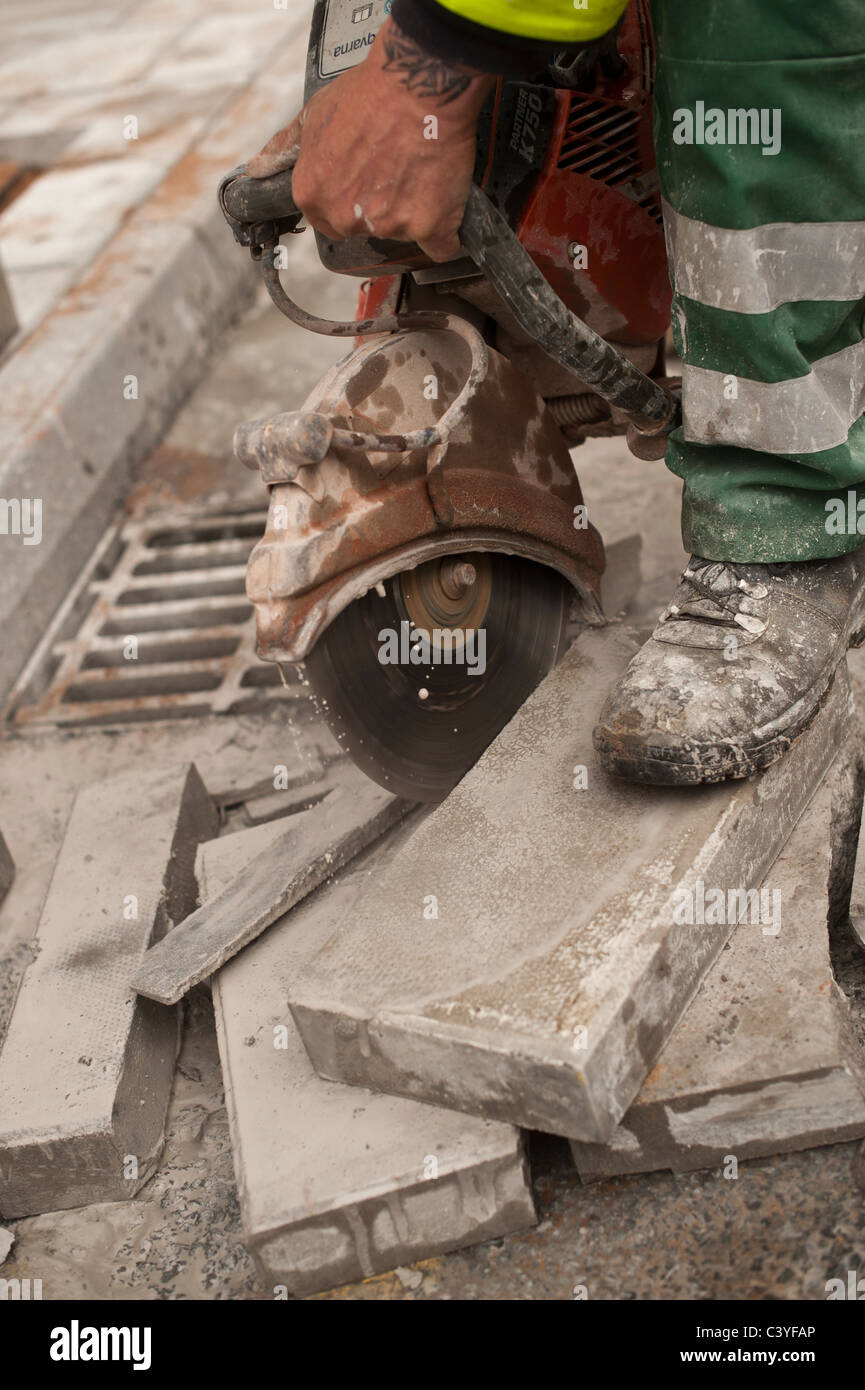 Dirty noisy dusty work; a man using an angle grinder to cut a paving stone, UK - Stock Image