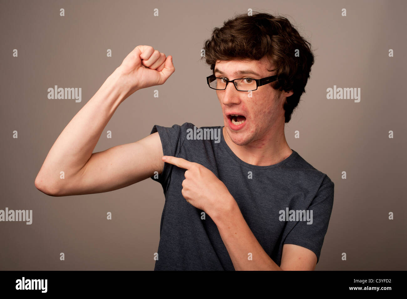 a spotty faced weak feeble geek nerd young man with thin arms wearing glasses flexing his muscles UK - Stock Image