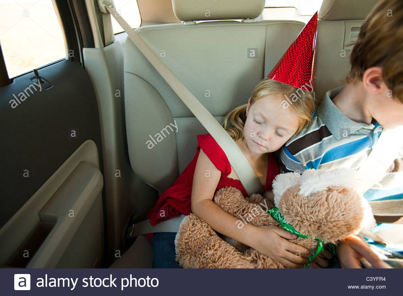 Two children in back seat of car, girl asleep - Stock Image
