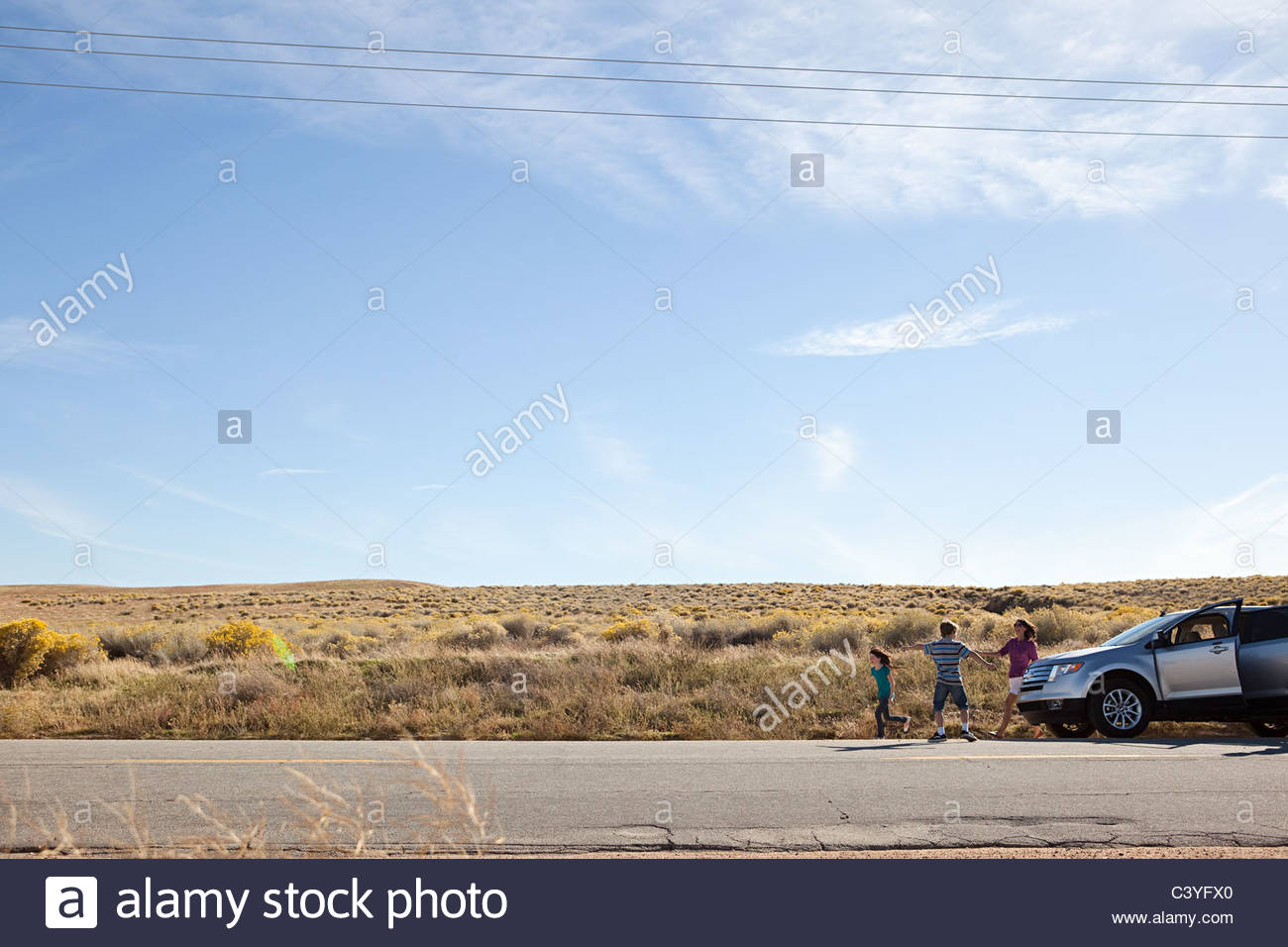 Three children by parked car in desert - Stock Image
