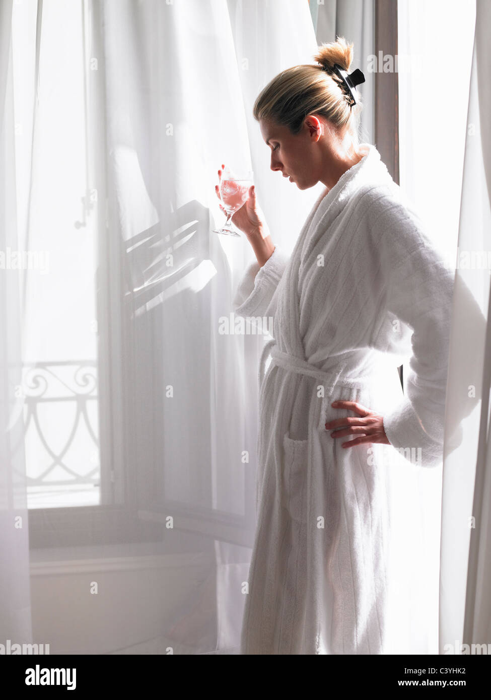 Woman in bath robe by the window - Stock Image