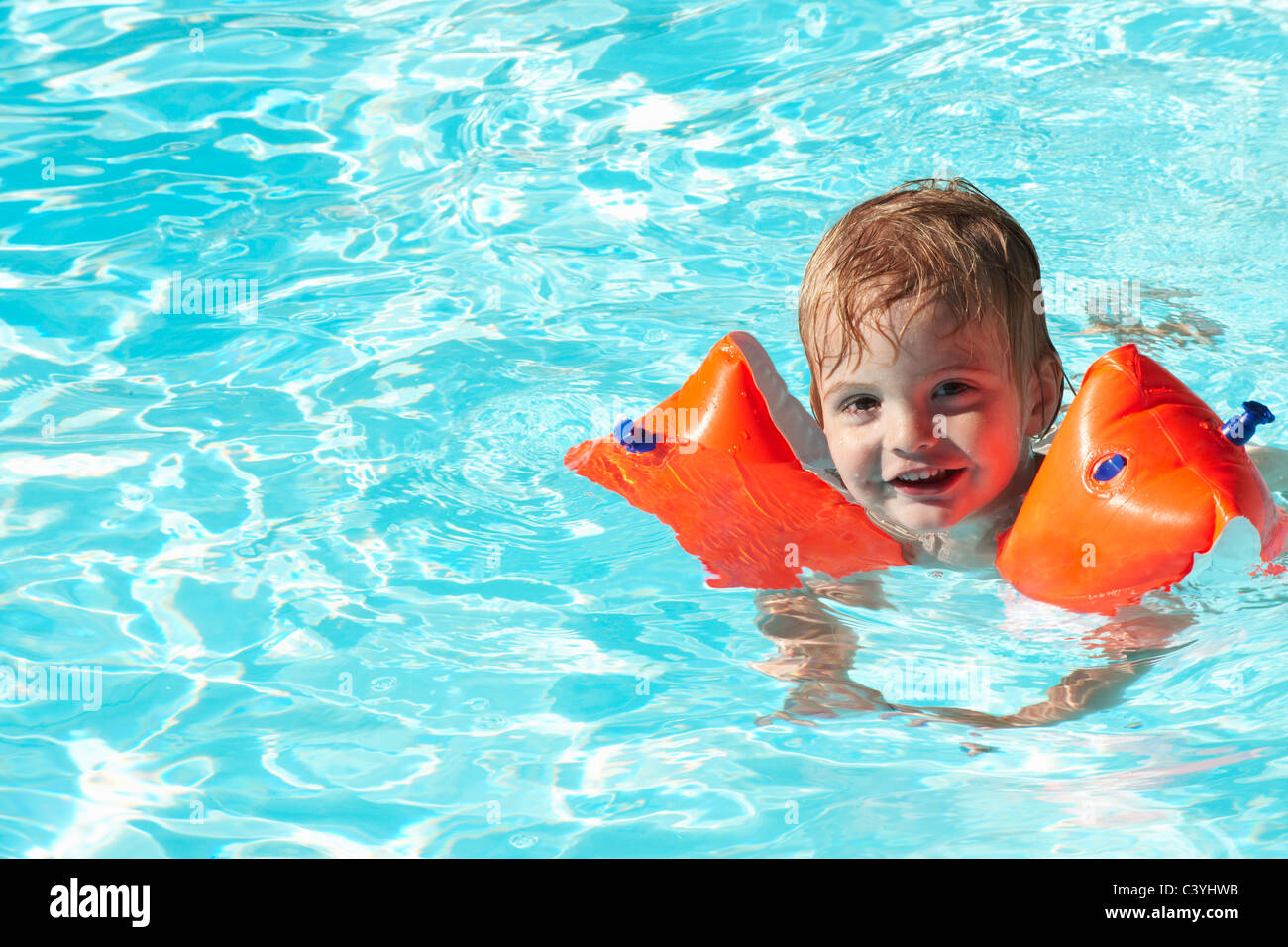 Baby boy swimming with water wings - Stock Image