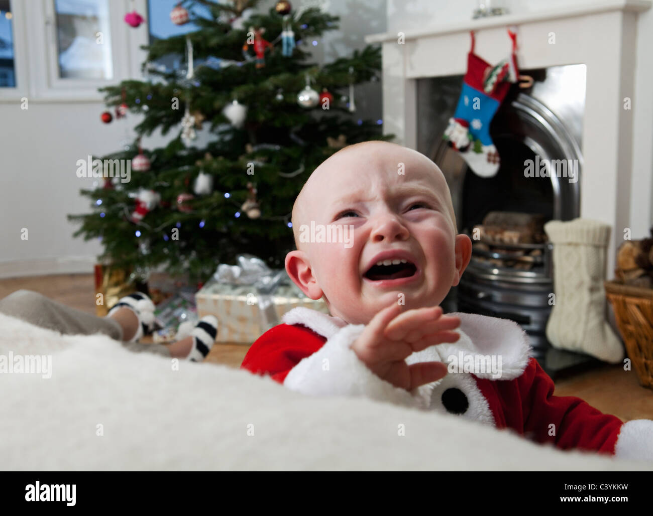 A baby crying at Christmas Stock Photo