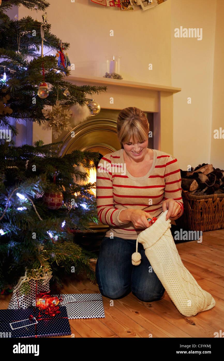 A woman reaching into a xmas stocking - Stock Image