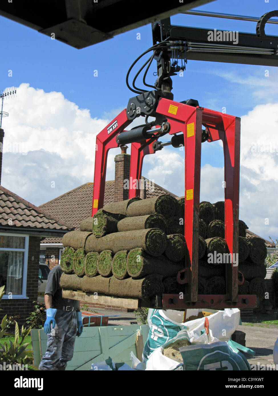 lorry delivering rolls of turf using the grabber - Stock Image