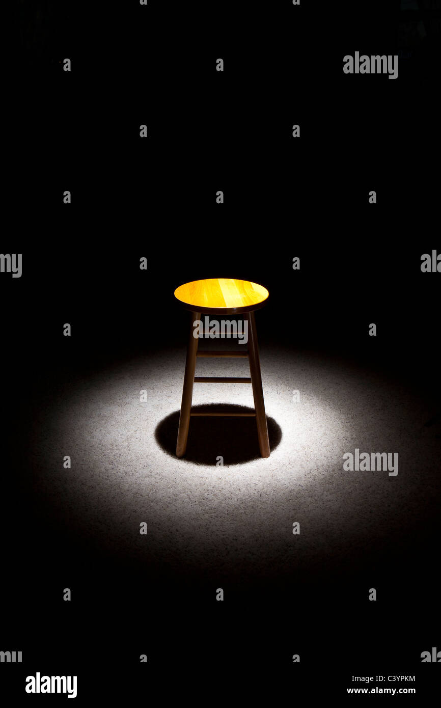 Lone Wooden Stool In Spotlight With Shadow And Black Background