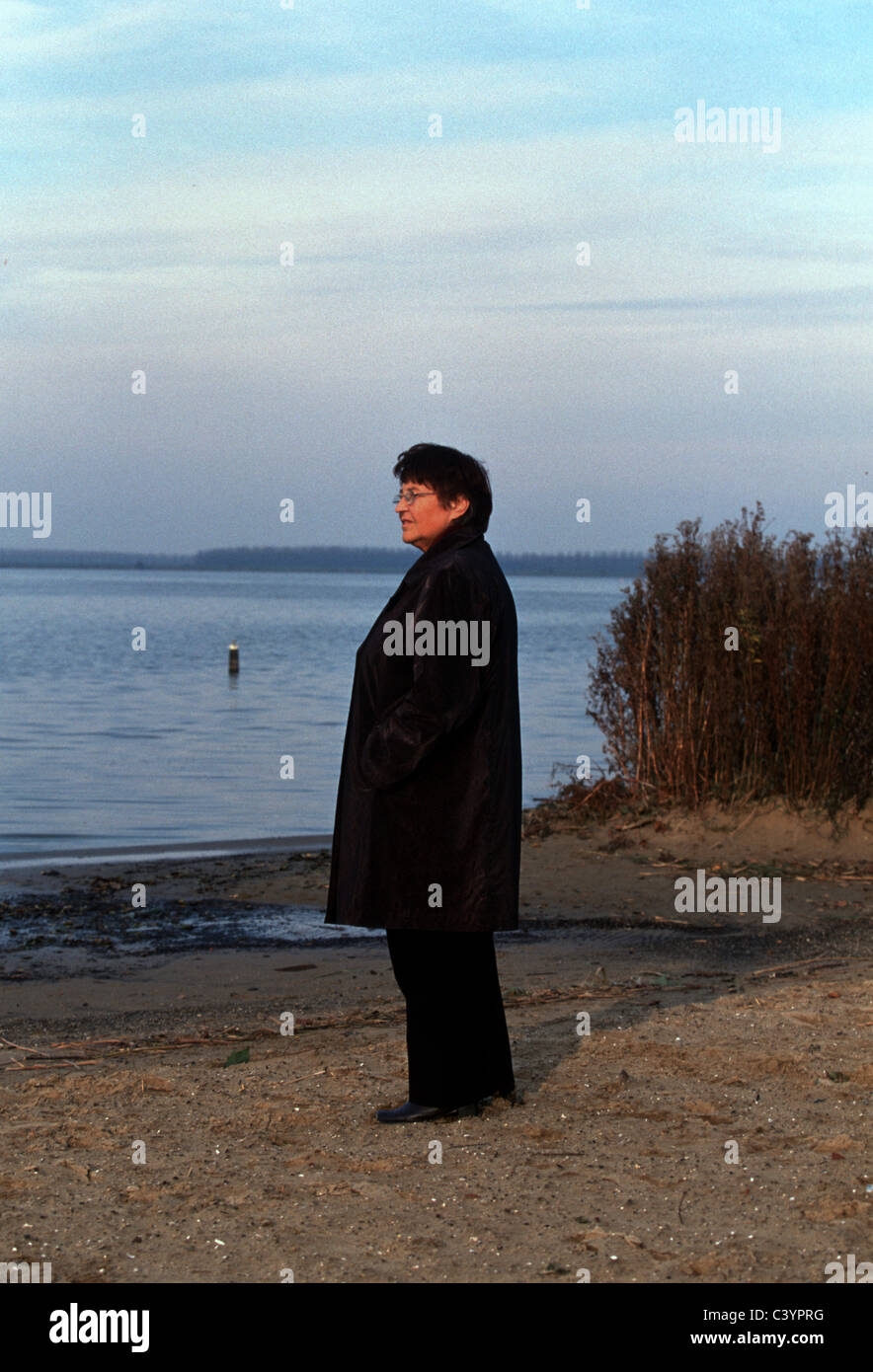 Old woman contemplating outside - Stock Image