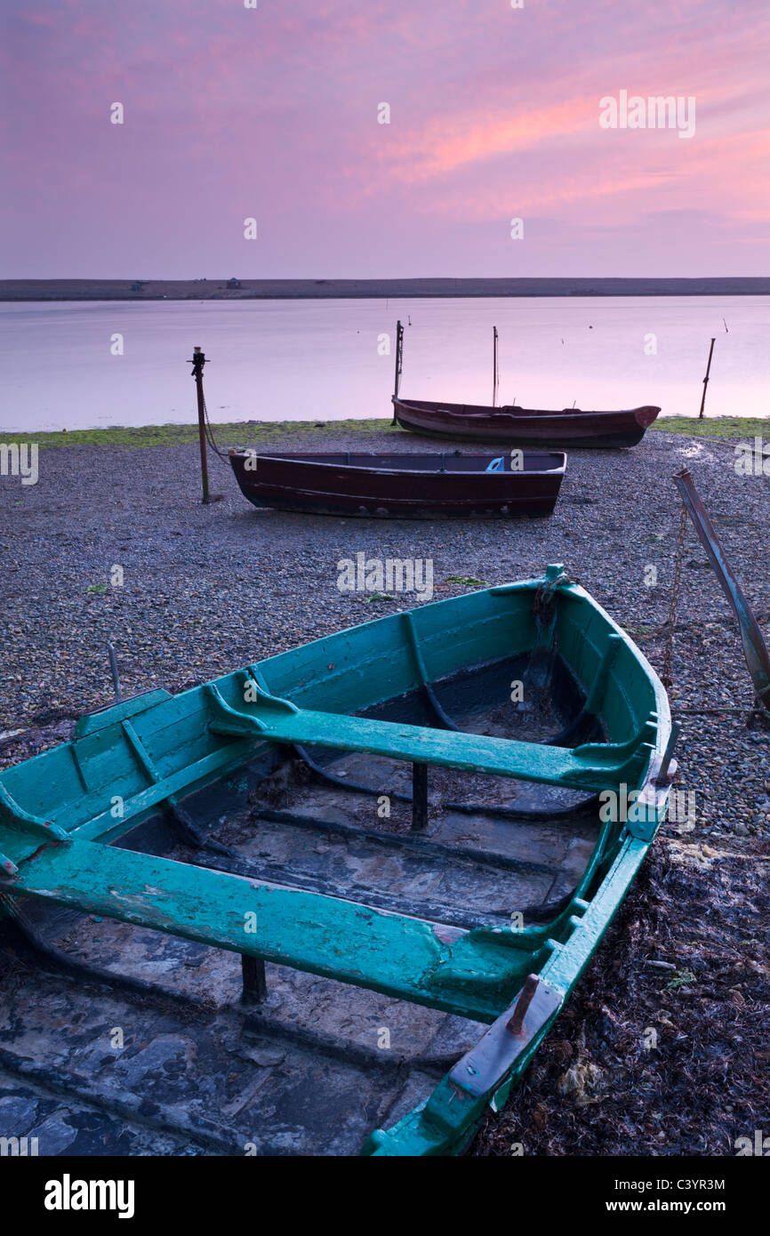 Boats at low tide on the shore of The Fleet lagoon, Chesil Beach, Dorset, England. Spring (March) 2011. - Stock Image