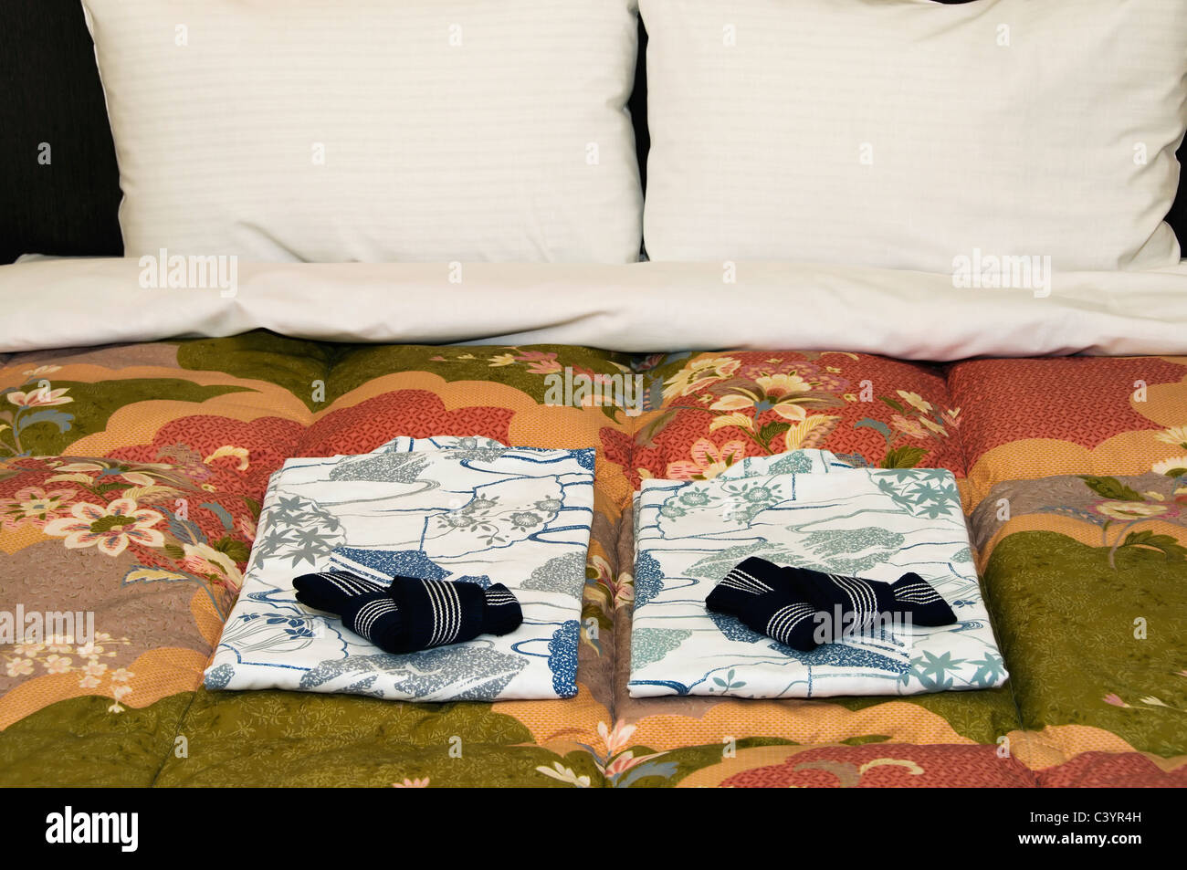 Matching cotton kimonos are placed on the bed for the comfort of guests. - Stock Image