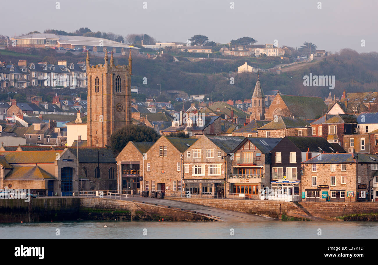 St Ives Parish Church, shops and tightly packed houses overlook the picturesque harbour at St Ives, Cornwall, England. Stock Photo